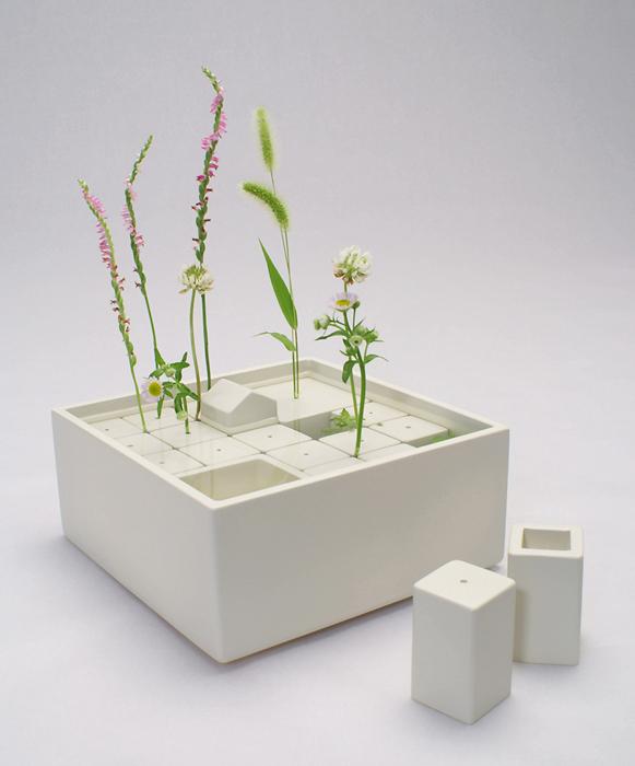 積み木のようなブロックの隙間や穴に雑草たちを活け、家の庭のような景色をつくります。